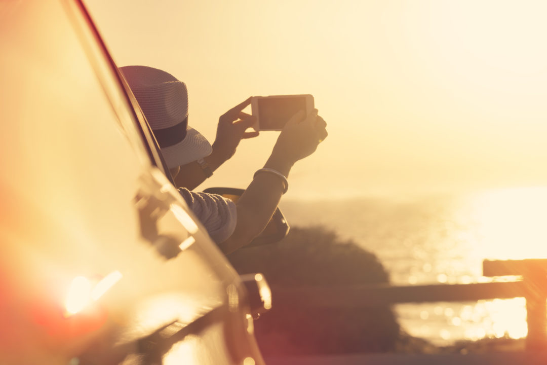 Woman taking a sunset photo in a car. Mature age woman using a smart phone to take a picture of the sunset over the ocean. She is on vacation or a road trip leaning out of the window and wearing a hat. Sun is reflected on the water